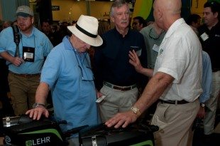 LEHR founder and CEO Bernard Herzer (left) explains the benefits of his propane outboard motor to West Marine founder Randy Repass (center) at the Miami Boat Show