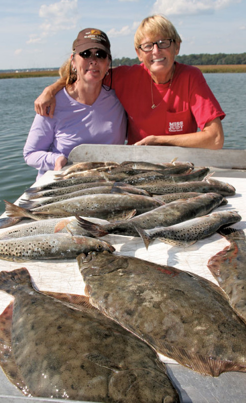 Tina Robertson and Captain Judy Helmey (red shirt) display a fine catching affair. On the old fish cleaning table there is some nice spotted sea trout and flounder!