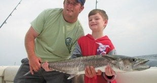 Josh Huffmaster helps Kody hold his prized king mackerel. Photo courtesy of Catch-A-Dream