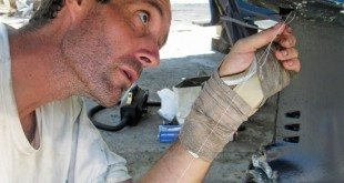 Surgery on the boot of one of the saildrives; Mark is sewing a little rip – a new skill! Photo by Liesbet Collaert