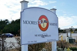 "Moores Marine Yacht Center sign MMYC has a logo with two burgees flying in opposite directions. The ""M"" stands for Moores and the trumpet with scrollwork represents the yacht center with a nod to the boats that have signature scrollwork along their bow. Photo Credit: Helen Aitken"