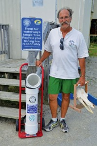 "Keith Rittmaster poses beside his mobile monofilament recycling bin. He's holding ""Lionel"" the 6- month old bottlenose dolphin that has fused fishing line in and around its jaws. Photo by Helen Aitken"