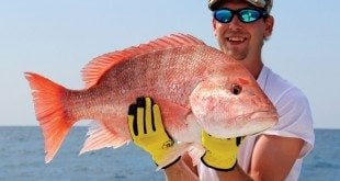Chad Rogers-Coxhead is holding up a nice genuine red snapper. Photo by Captain Judy Helmey