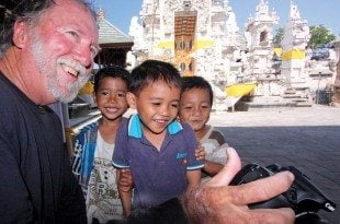Youngsters in a temple in Bali look at their picture on Fatty's camera
