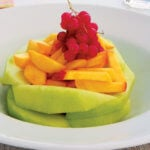 A DELICIOUS FRUIT FINISHER: Sliced melon, Sliced peaches, Sprig of cranberries. This is something very simple, but very beautiful; a presentation by Elizabeth Love.